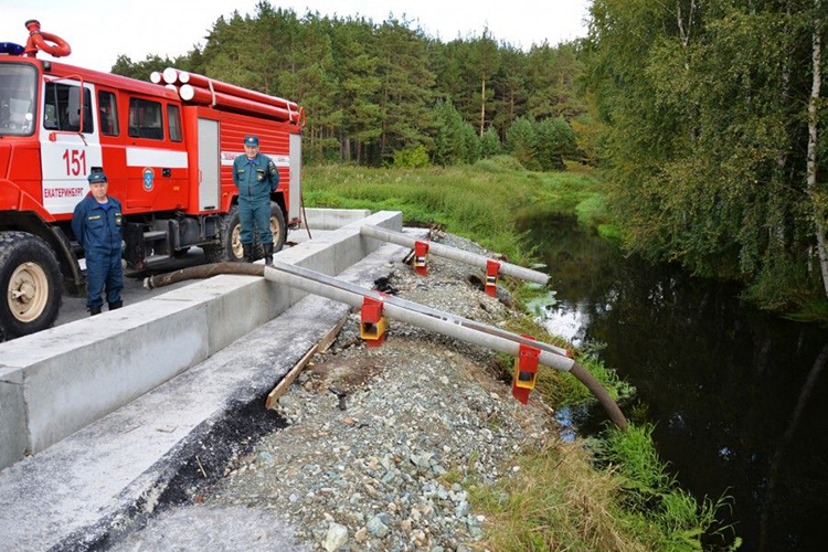 Забор воды пожарной машиной из водоема через заграждения